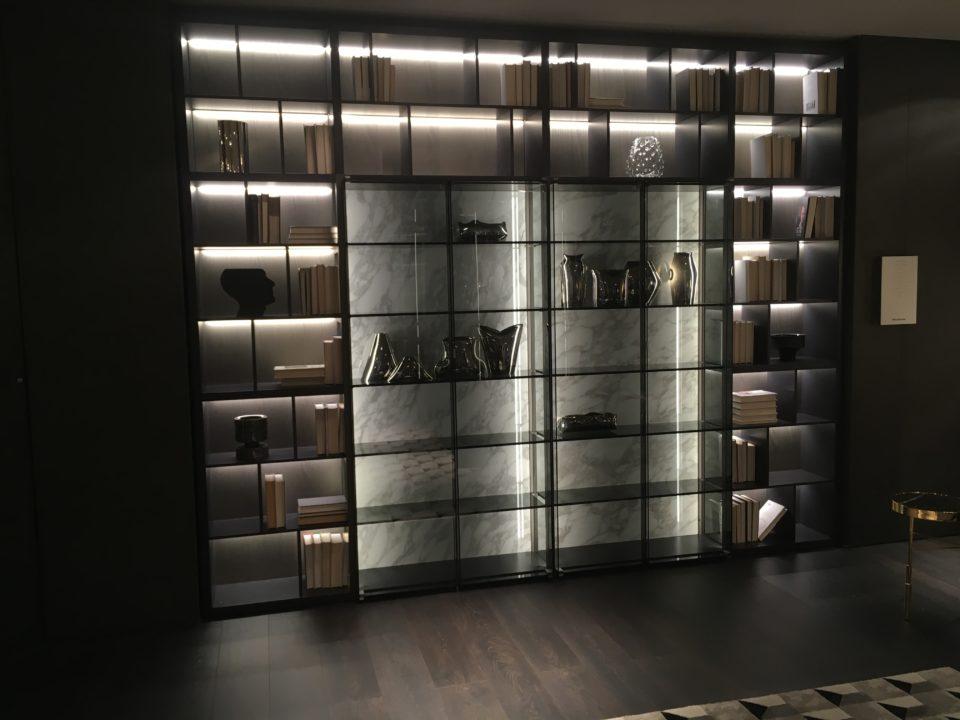 Targi wnętrz Mediolan 2018 - elegancki regał, w ciemnym wydaniu, z kamiennymi plecami, szkłem i ciemnymi ramami.