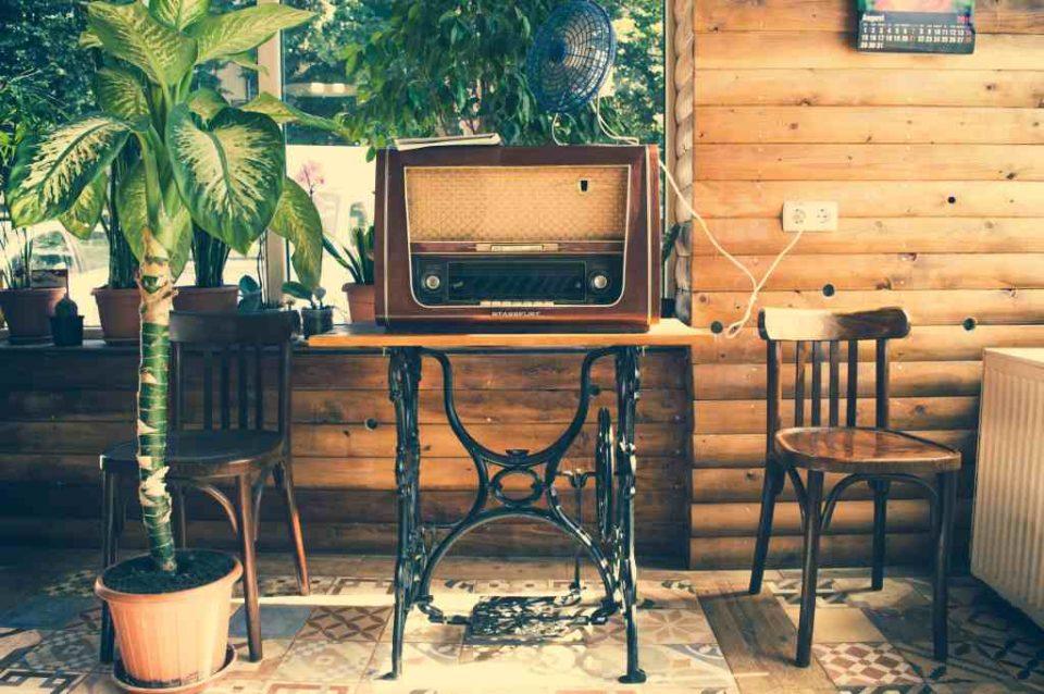 Stelaż ze starej maszyny, drewniane krzesła i dużo zieleni